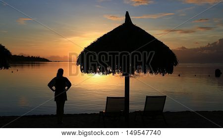 Silhouette of woman and beach umbrella at the sunset in the ocean. Moorea Island French Polynesia