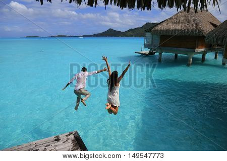Happiness jump of young couple on the water. Over water bungalows at Bora Bora French Polynesia.