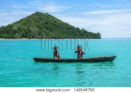 Happy sea Gypsy kids on a canoes in Bodgaya Island in Tun Sakaran marine park,Semporna,Sabah Borneo,Malaysia.