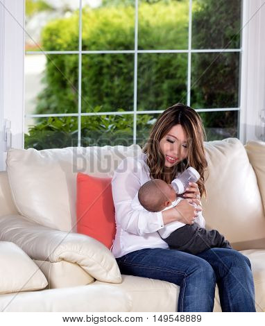 Mother feeding young baby infant boy on family white sofa with large windows in background
