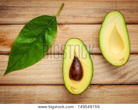 Fresh Avocado With Avocado Leaves On Wooden Background. Organic Avocado Healthy Food Concept.