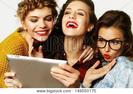 three teen girls friends taking selfie with digital tablet, studio shot over gray background