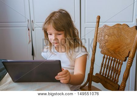 Cute little girl sitting against the wall and using tablet computer