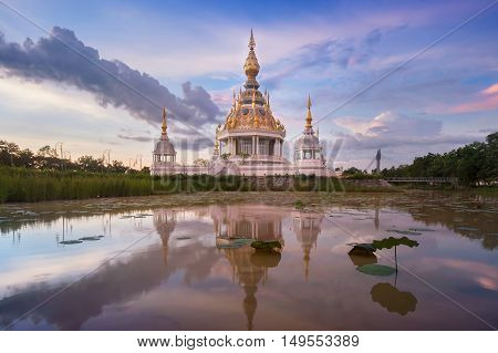 Buddha temple in lotus lagoon of Thailand during sunset