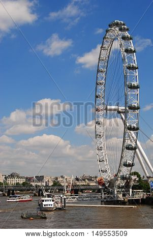 London, United Kingdom - June 21, 2014. Thames River waterfront with the London Eye, cruising boats, bridge and boats in the distance.