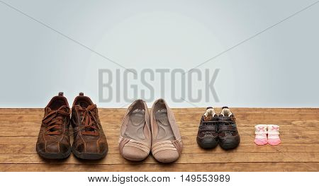 Family of Fours Shoes in a Row on a Wooden Surface