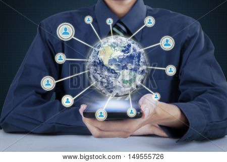Image of businessman holding cellphone with 3d earth globe in cellphone connecting on all people