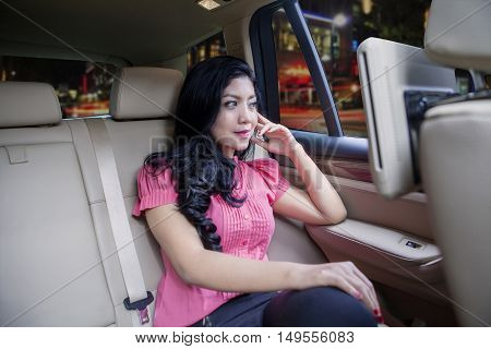Image of businesswoman sitting on a car backseat and looking through the window on the road
