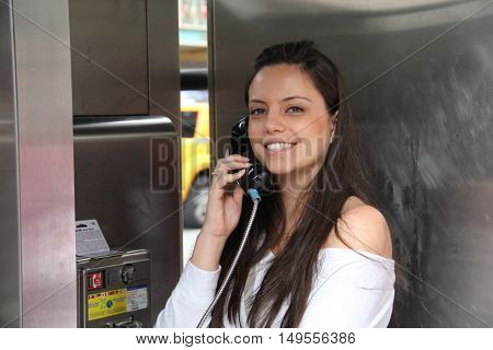 Happy pretty young girl talking by public telephone. Communication concept.