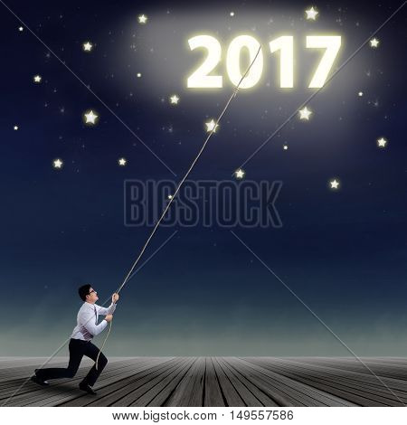 Young business man using a rope to pull number of 2017