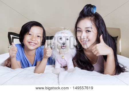Happy little girl and mother showing thumbs up while playing with their puppy in bedroom