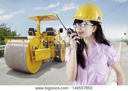 Image of pretty young businesswoman using walkie talkie with a backhoe on the street