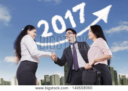 Portrait of three entrepreneurs shaking hands with cloud shaped number 2017 and upward arrow