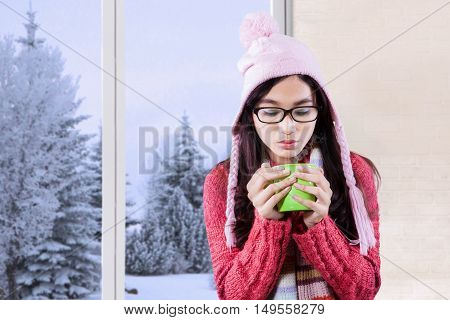 Portrait of pretty young woman wearing knitted and holding cup of hot drink at home winter season in the window