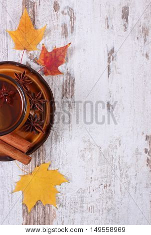 Cup Of Tea With Lemon, Spices And Autumnal Leaves On Wooden Background, Copy Space For Text