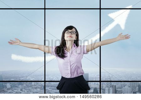Young businesswoman celebrating her success and raising hands in the office with an upward arrow in the sky