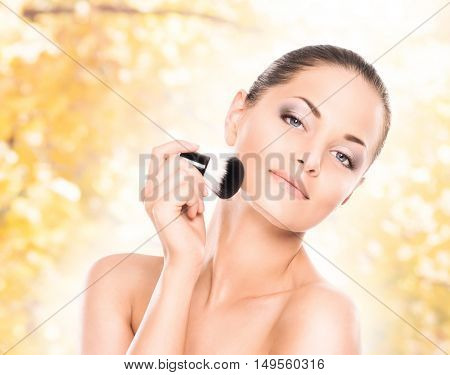 Beauty portrait of young, attractive, fresh, healthy and natural woman with the makeup brush over seasonal autumn background
