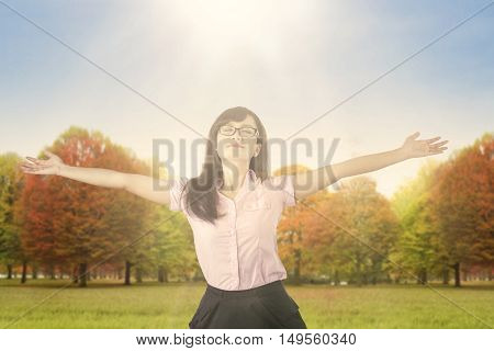 Young woman raising her hands and enjoying the fresh air in the park with the sun is shining.