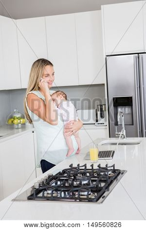 Mother talking on mobile phone while carrying her baby in kitchen at home