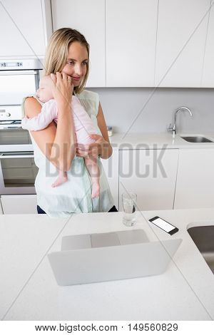 Mother carrying her baby in kitchen at home