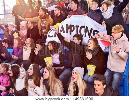 Sport fans holding champion banner and eating popcorn on tribunes. Group people.