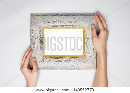 A female hand hold a wood photo(picture) frame isolated white top view at the studio.