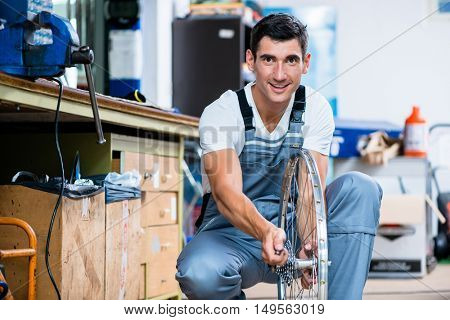 Man as bicycle mechanic working in workshop