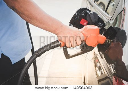Car refueling on petrol station. Fuel pump at station. Man pumping gasoline fuel in car at gas station.