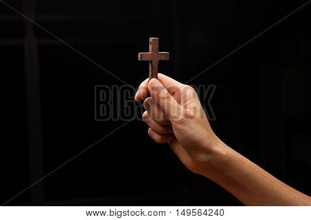 Hands with a cross with dark background