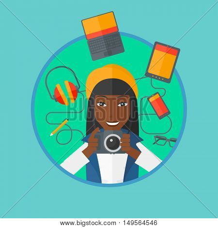 An african woman taking photo with digital camera. Woman surrounded with electronic gadgets. Woman using many electronic gadgets. Vector flat design illustration in the circle isolated on background.