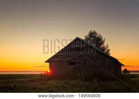 Summer Sunset Behind A Barn House
