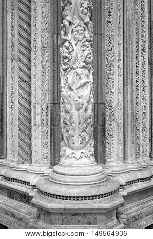 Cathedral of Siena (Tuscany, Italy): detail of a facade marble ornamental column, finely inlaid with bas-reliefs. Black and white photo.