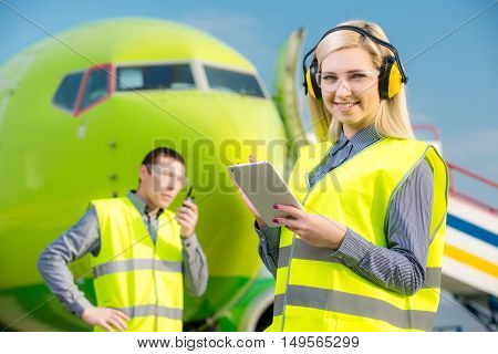 Aircraft workers with radio standing in front of a commercial airliner