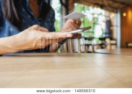 Beautiful young asian woman using smartphone and holding card for shopping online payment . Shopping concept with copy space. Online shopping concept.