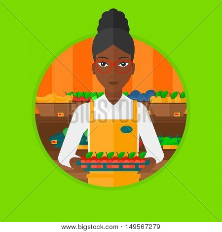 An african-american supermarket worker holding a box with apples. Young supermarket worker carrying box with fruits in supermarket. Vector flat design illustration in the circle isolated on background