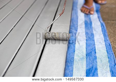 Worker painting steel bars with paintroller on construction site