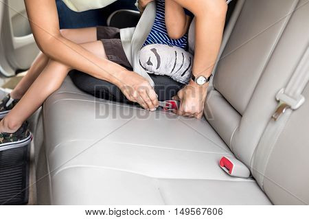 Mother is fasten seat belt with car seat to child for protection and safety
