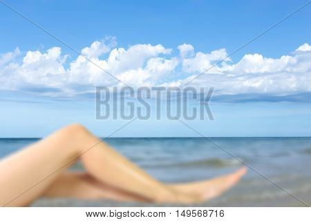 Blurred womans leg with blue sky and white cloud backgroud