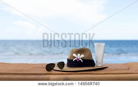sunglasses and hat and sunblock with flower and the sea in background