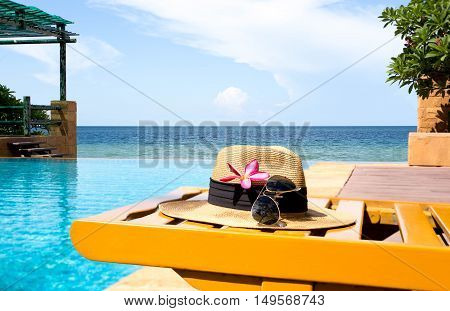 Sunglasses and hat and swimming pool with flower and the sea in background