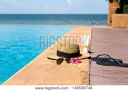 Hat sunglasses and flip flops next to swimming pool with beach backgroun