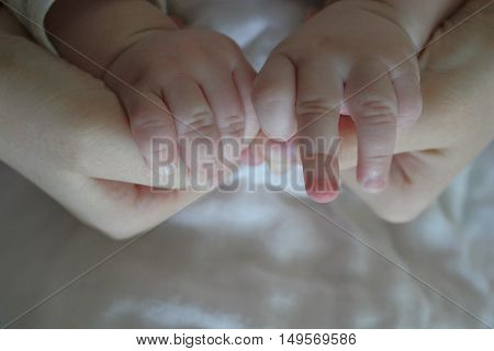 Baby Hand reaching for an adult hand - close-up