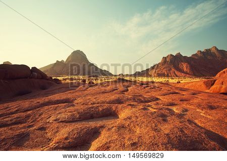 Colorful landscapes of the orange rocks in the Spitscoppe mountains in Namibia on a sunny hot day.