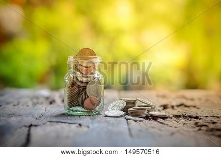 Saving money coins in the bottle on wooden background