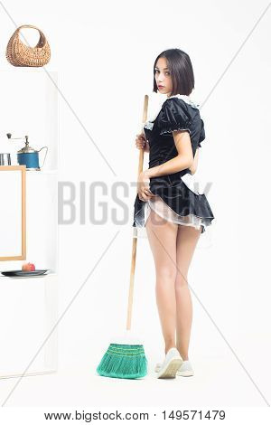 Young girl with pretty face in sexy beautiful black maid servant costume posing with green sweep broom near kitchenware on shelves isolated on white background