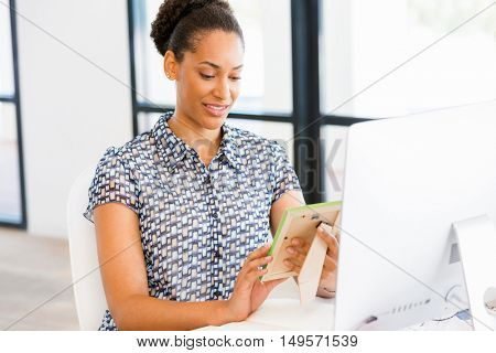 Portrait of smiling afro-american office worker in offfice holding a photo frame