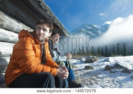 Two young men are resting on wooden bench in winter mountains outdoors