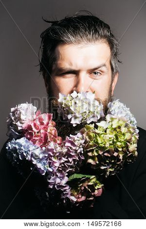 handsome sexy bearded young man hipster with floral beard and mustache on serious face in studio holding hydrangea flower bouquet on grey background closeup