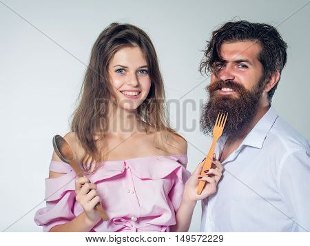 Young Couple With Wooden Spoon And Fork