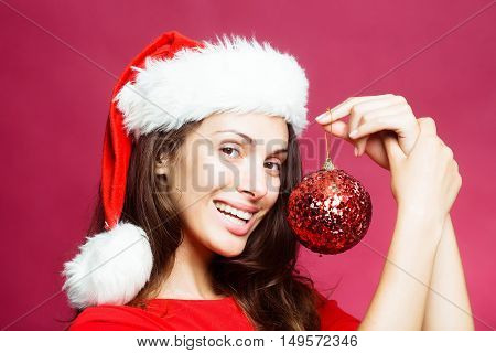 young sexy new year woman or girl with long brunette hair and pretty face in red christmas santa claus holiday hat holds decorative ball in studio on pink background